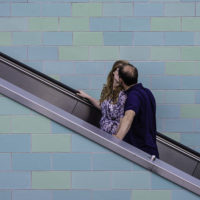 Couple kissing on an up escalator