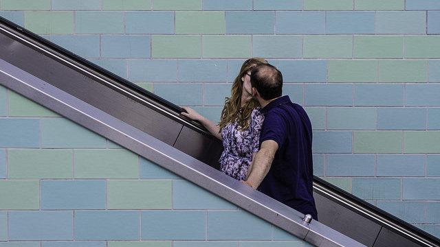 Couple kissing on an up escalator